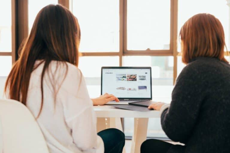 two women looking at a website on laptop