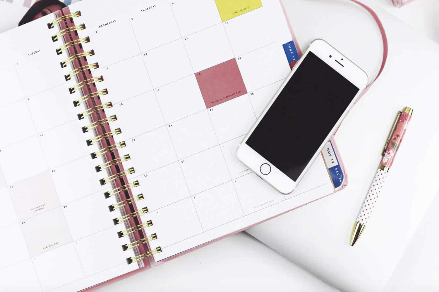 Calendar planner open with pen and cellphone on table
