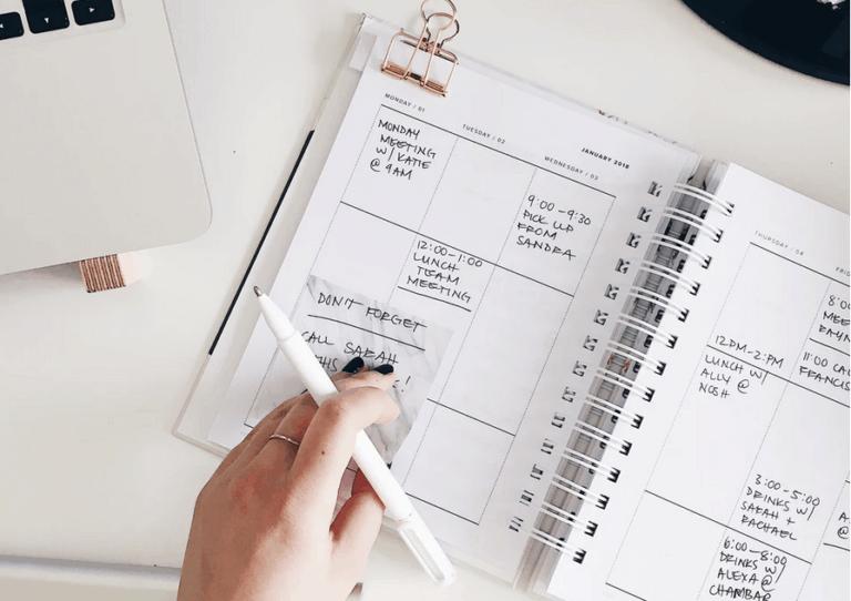 Person using a calendar planner notebook