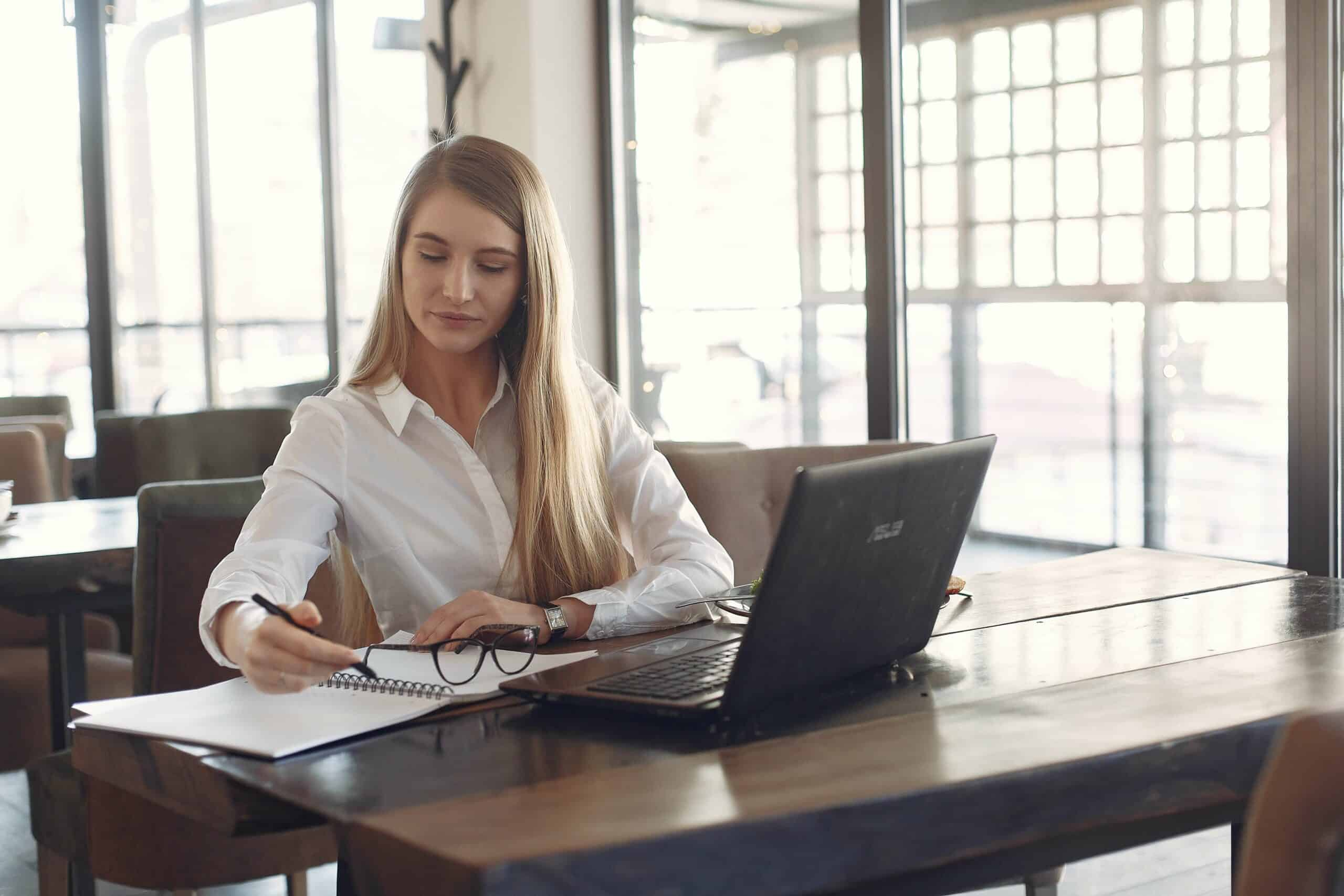 Business woman sitting at desk with laptop and writing on notepad