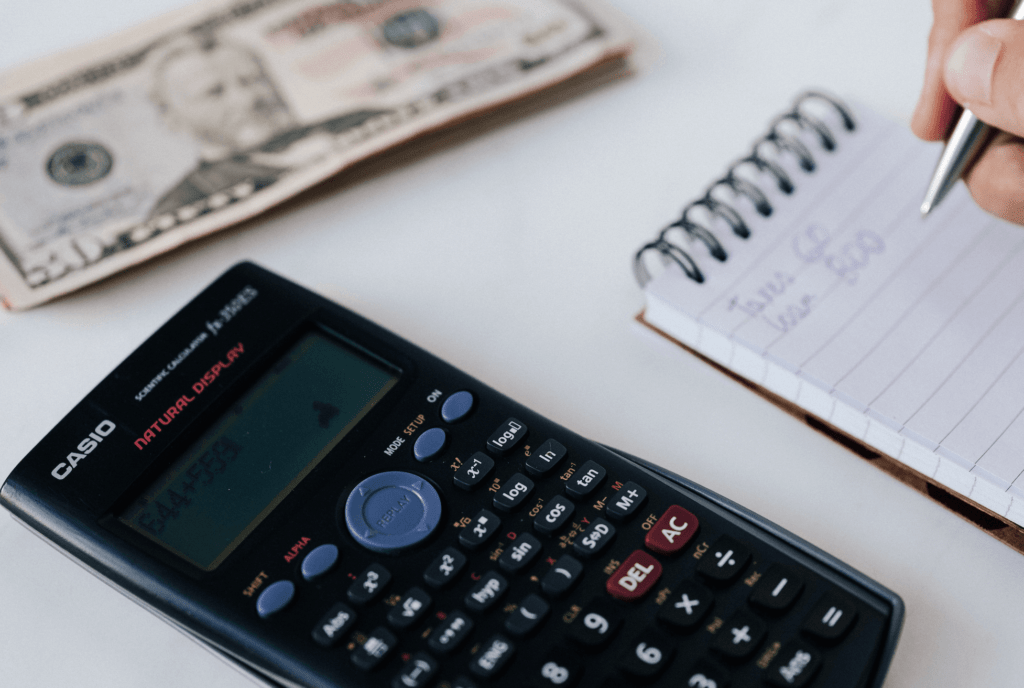 Desk with calculator and US dollars and person writing on notepad