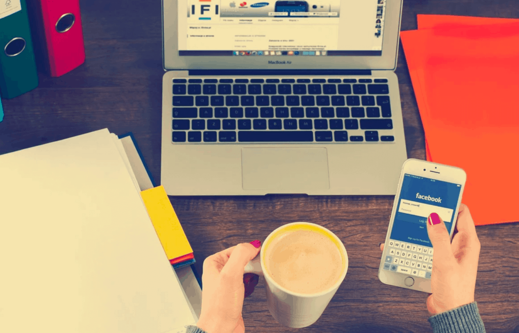 Woman sitting at desk with laptop, binder, and coffee cup looking at cellphone with Facebook sign-in page open
