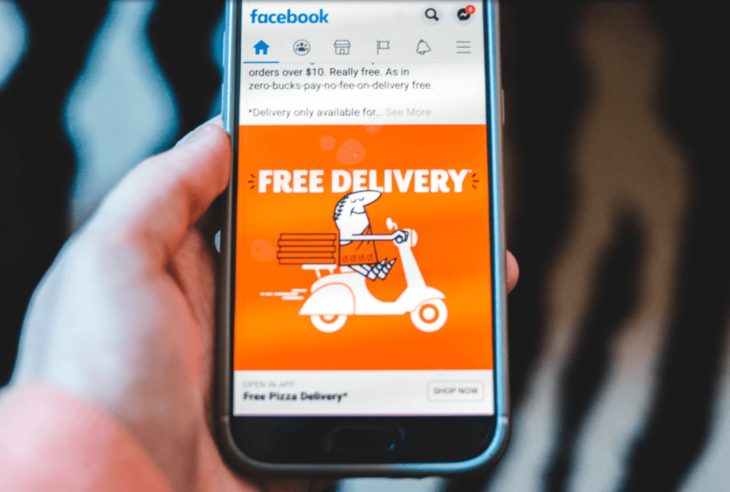 Cellphone showing Facebook ad for free pizza delivery