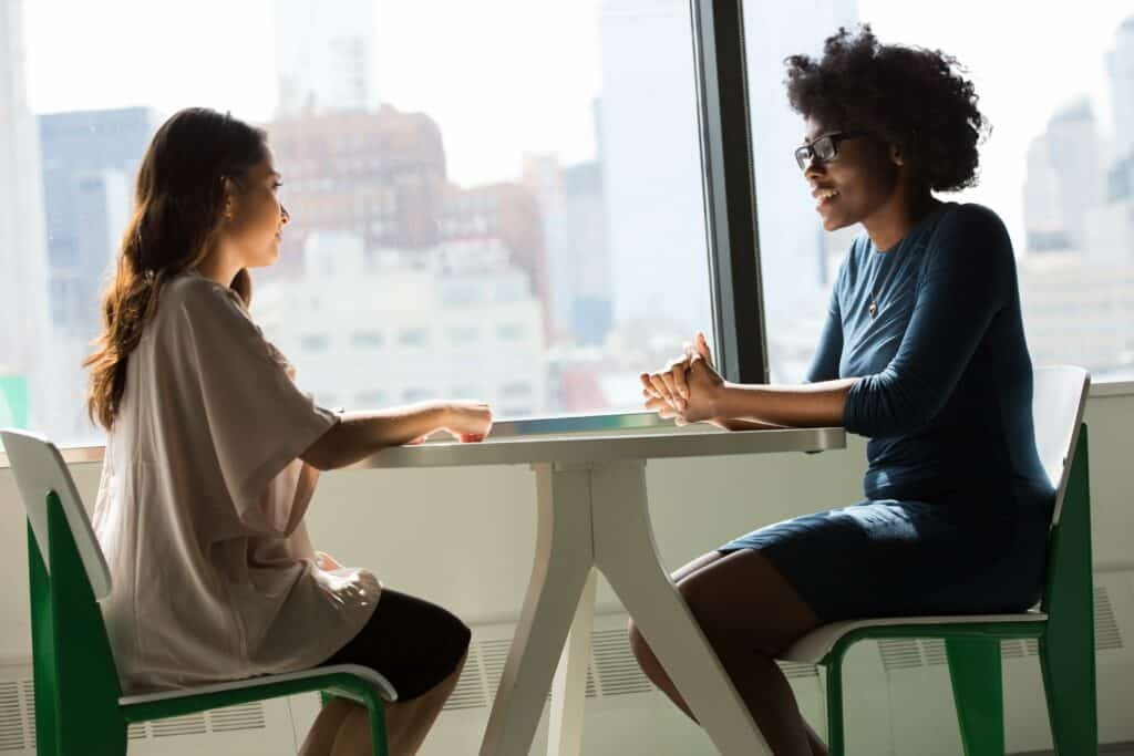 Two women sitting at a table having a meeting