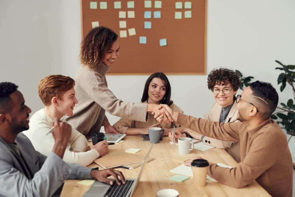 Six people sitting at a desk in a meeting with two people shaking hands