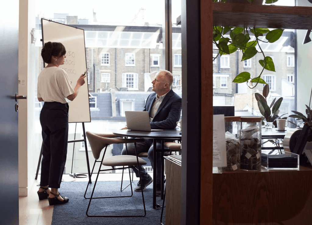 Woman presenting business presentation to man in office