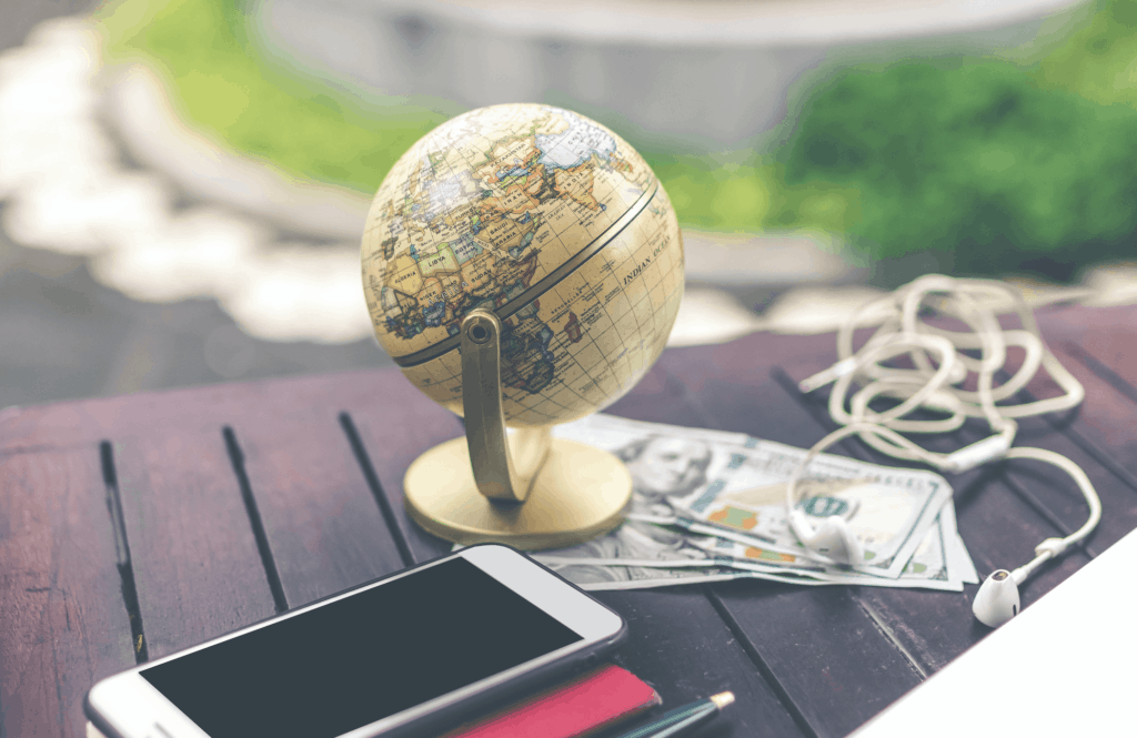 Table with cellphone, stationary, globe, money, and headphones