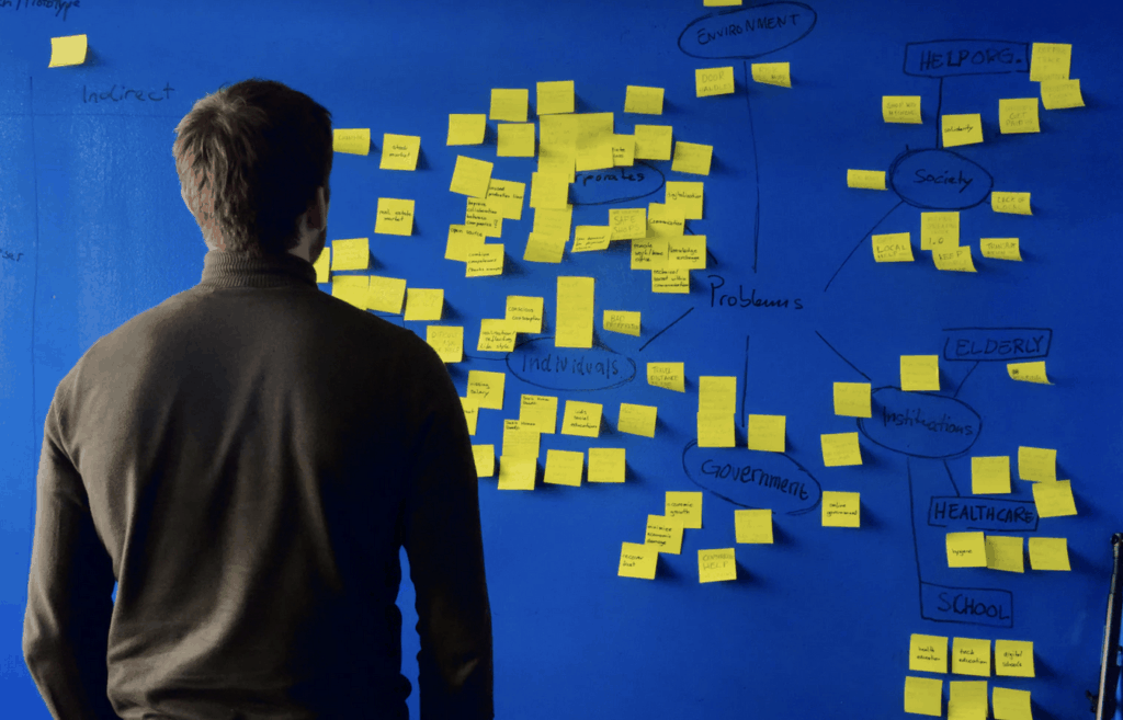 Man looking at wall with sticky notes on