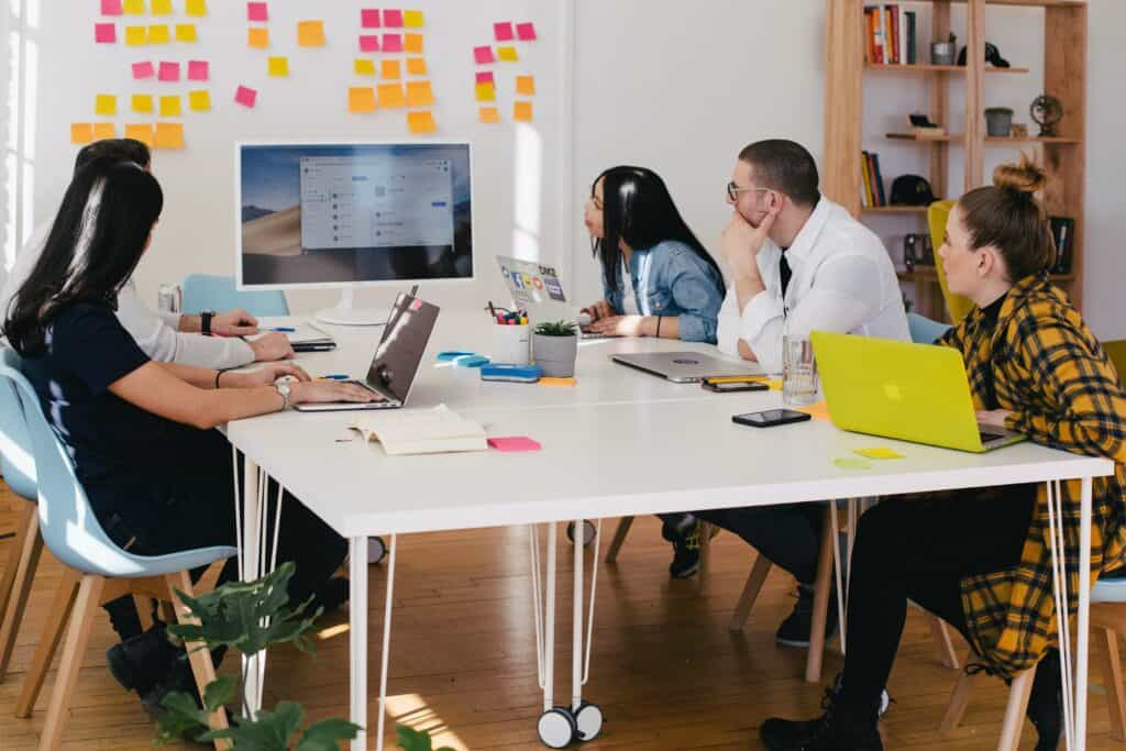 Employees in a meeting sitting around a table and looking at screen
