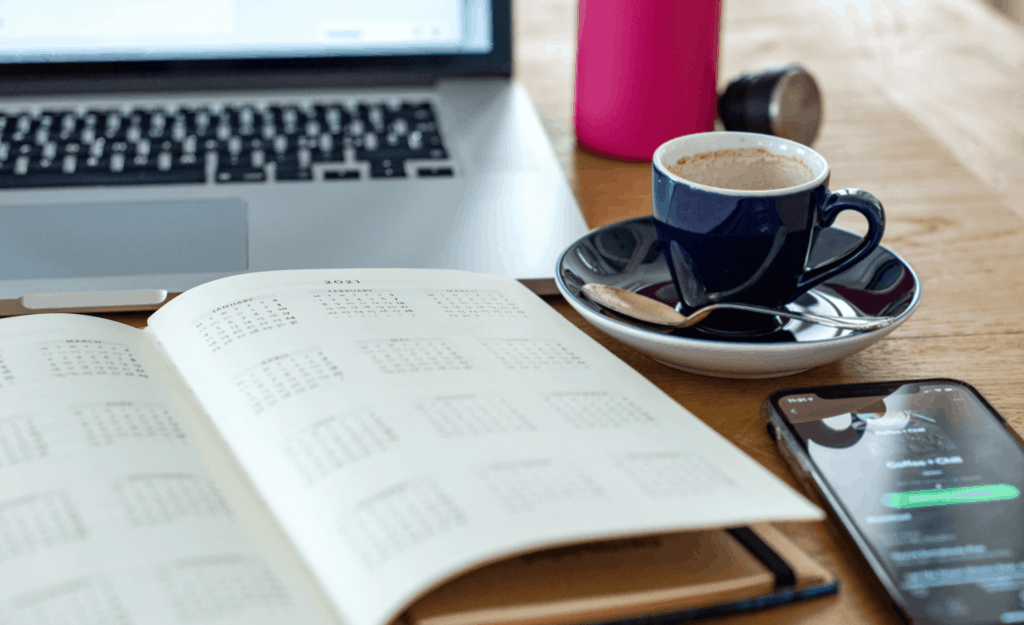 Calendar notebook open on table with laptop, cellphone, and coffee cup