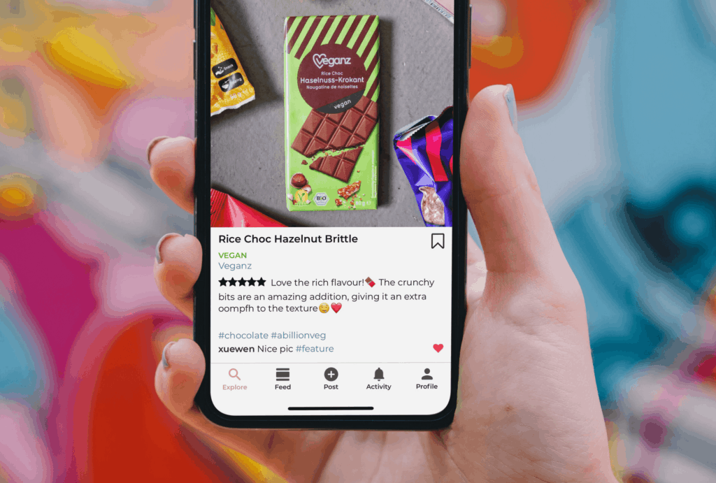 person holding cellphone showing review and comments on an ecommerce post promoting vegan chocolate