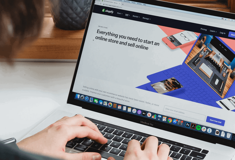 Person using laptop to edit ecommerce website on shopify
