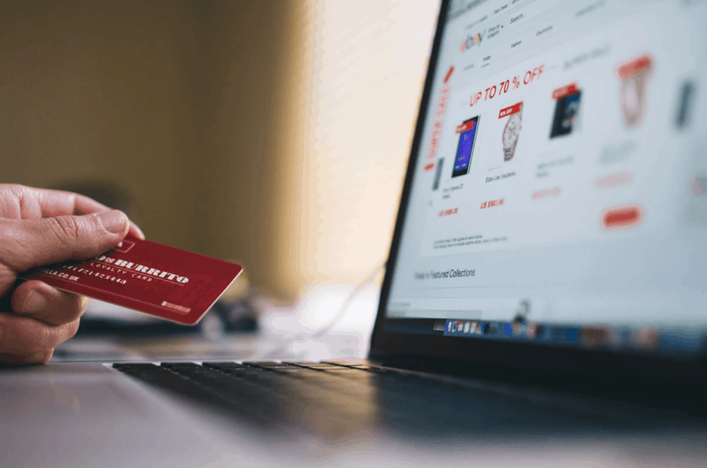 Person using laptop to make ecommerce purchase with credit card