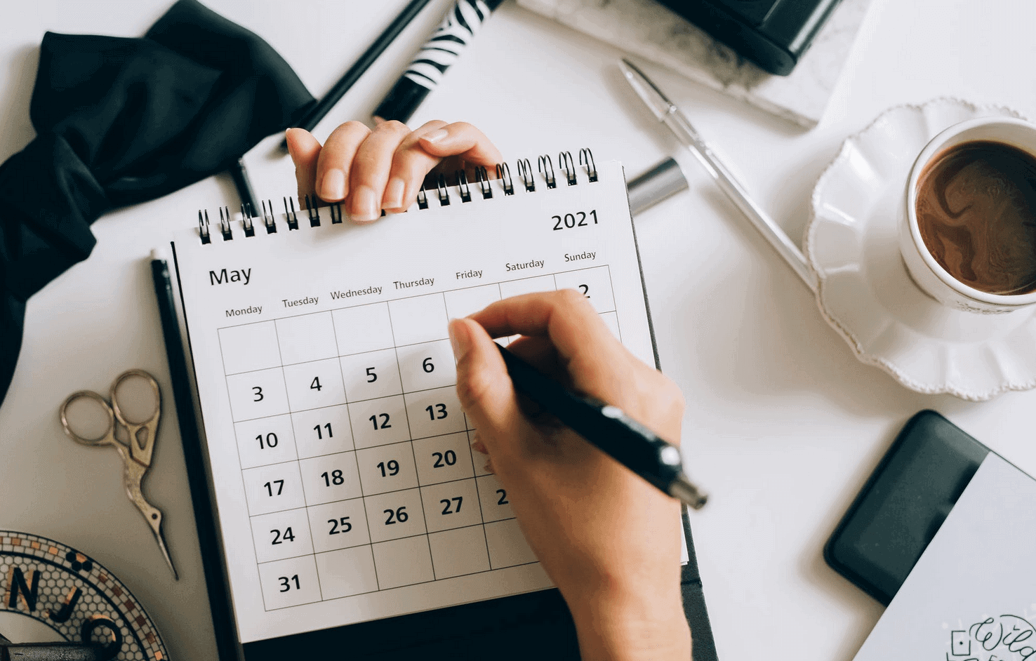 Person writing on May 2021 calendar