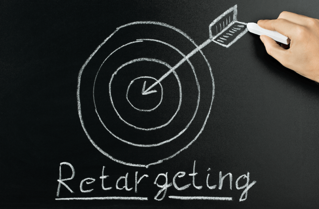 Chalk board showing someone drawing an arrow and target with the words retargeting